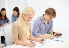 有笔记本的微笑的学生在学校 库存图片