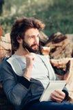 有笔记本的想法的人在堆木头 免版税库存照片