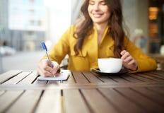有笔记本的愉快的在咖啡馆的妇女和cappucino 库存照片