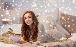 有笔记本的愉快的少妇在床上在家 图库摄影