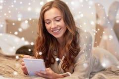 有笔记本的愉快的少妇在床上在家 免版税库存照片