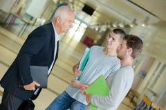 有笔记本的教授谈话与走廊的学生 库存图片
