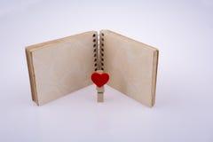 有笔记本的有之心的夹子 图库摄影