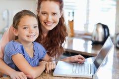 有笔记本的母亲和女儿在厨房里 库存图片