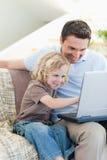 有笔记本的父亲和儿子在沙发 免版税库存图片