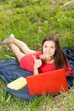 有笔记本的美丽的女孩显示赞许 免版税库存图片
