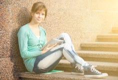 有笔记本的美丽的少妇学生 室外学员 免版税库存照片