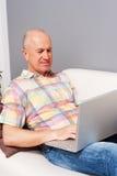 有笔记本的老人在家 免版税库存照片