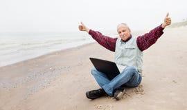 有笔记本的老人在海滩 免版税图库摄影