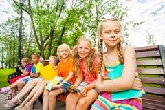 有笔记本的逗人喜爱的孩子坐长凳 免版税库存图片