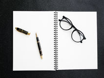 有笔记本的钢笔在署名概念的黑织地不很细背景 库存照片