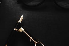 有笔记本的钢笔在署名概念的黑织地不很细背景 免版税图库摄影