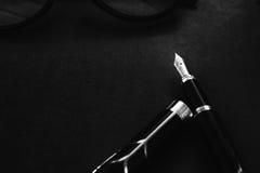 有笔记本的钢笔在署名概念的黑织地不很细背景 免版税库存照片