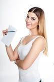有笔记本的年轻学生计划她的女孩和笔穿偶然白色T恤杉的每日日程表在白色 演播室被修饰的射击 免版税库存图片