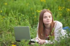 有笔记本的年轻微笑的妇女在看笔记本计算机的公园 图库摄影