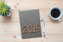 有笔记本的2019新年快乐、无奶咖啡杯子、笔和玻璃在木桌上,顶视图和拷贝空间 新的开始,目标,R 免版税库存照片