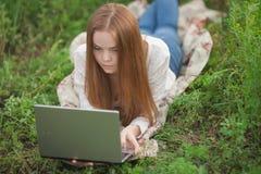 有笔记本的年轻seriois女学生女孩在看笔记本计算机的公园 库存图片