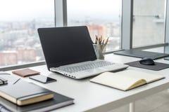 有笔记本膝上型计算机舒适的工作表的工作场所在办公室窗口和城市视图 免版税库存照片