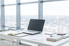 有笔记本膝上型计算机舒适的工作表的工作场所在办公室窗口和城市视图 库存图片