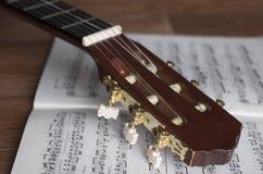 有笔记的吉他床头柜关于木背景 免版税库存图片
