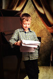 有笔记的男孩在他们的站立在钢琴附近的手上 免版税图库摄影
