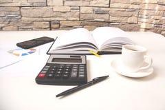 有笔记薄和电话的计算器在书桌上 免版税库存图片