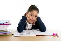 有笔记薄的愉快的拉丁矮小的学校女孩微笑回到学校和教育概念的 库存图片