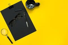 有笔记薄的,杯子,笔营业所小配件平的位置显示,开发,玻璃和等 顶视图 黑办公室 免版税图库摄影