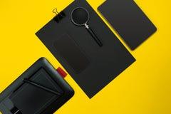 有笔记薄的,杯子,笔营业所小配件平的位置显示,开发,玻璃和等 顶视图 黑办公室 库存照片