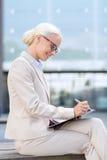 有笔记薄的年轻微笑的女实业家户外 免版税库存照片