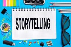 有笔记讲故事的笔记本与在蓝色背景的办公室工具 概念讲故事 免版税库存照片