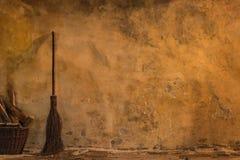 有笤帚和火木头的葡萄酒黄色墙壁 免版税库存照片