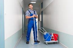 有笤帚清洁办公室走廊的愉快的男性工作者 免版税图库摄影