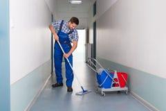 有笤帚清洁办公室走廊的男性工作者 免版税库存照片
