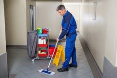 有笤帚清洁走廊的男性工作者 免版税库存照片