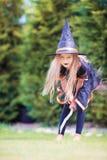 有笤帚的愉快的矮小的巫婆在万圣夜 窍门 免版税图库摄影