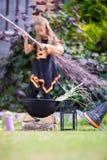 有笤帚的愉快的矮小的巫婆在万圣夜 窍门 图库摄影