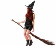 有笤帚的愉快的年轻巫婆,隔绝在白色演播室backgro 免版税库存照片