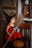 有笤帚的逗人喜爱的白肤金发的万圣夜巫婆女孩 免版税库存照片