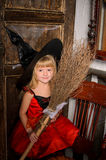 有笤帚的逗人喜爱的白肤金发的万圣夜巫婆女孩 图库摄影