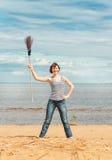 有笤帚的滑稽的妇女在海滩 库存图片