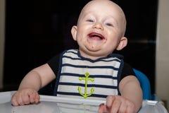 有第一颗牙的婴孩吃食物的 库存图片