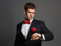 有等待和看时钟的花的英俊的人 年轻人衣服的新郎人 免版税图库摄影