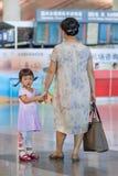 有等待在北京首都国际机场的祖母的逗人喜爱的女孩 免版税库存照片