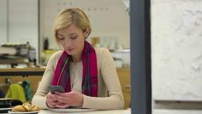 有等待在咖啡馆的表上的手机的翻倒妇女 股票录像