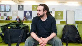 有等待在机场休息室的dreadlocks的英俊的年轻人 免版税库存照片