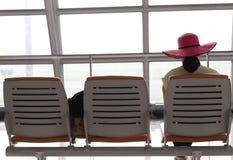 有等待在机场termin的一个桃红色帽子的妇女一次飞行 免版税图库摄影