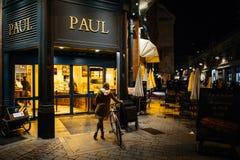 有等待在自行车的顾客的保罗Boulangerie和法式蛋糕铺 免版税库存照片