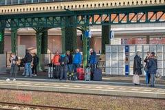 有等待火车的行李的旅行家在火车站 免版税库存图片