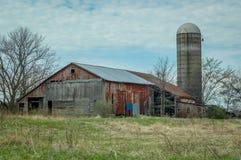 有筒仓的土气红色谷仓在乡下 免版税库存图片